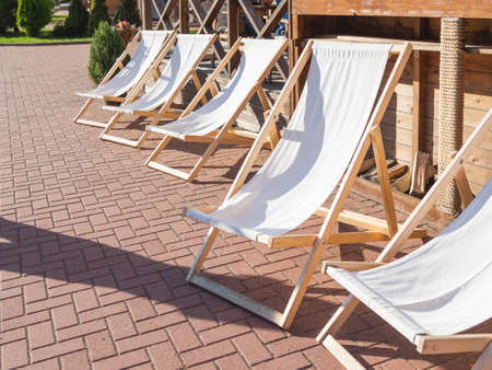 Deckchairs are at cafe's verandah. Visitors can enjoy the good weather and sunbathe in lounge chairs next to the restaurant. Rosa Khutor Alpina Ski Resort, Sochi, Russia.