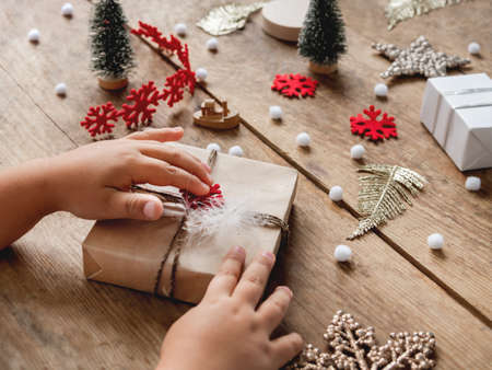 Child wrapped Christmas presents in craft paper with white fluffy pompons and fringe as decoration. Wooden table with hand made New Year gifts.