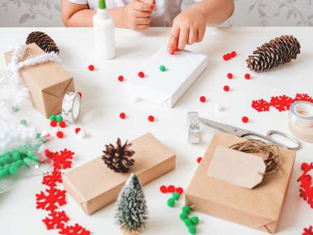 Kid wraps handmade Christmas presents in craft paper with colorful pompons and snowflake ribbons as decorations. Child prepares gifts for New Year celebration. Peaceful leisure activity before winter holidays.