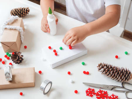 Kid wraps handmade Christmas presents in craft paper with colorful pompons and snowflake ribbons. Child prepares gifts for New Year celebration. Peaceful leisure activity before winter holidays.