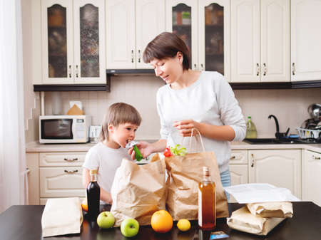 Woman and toddler sorts out purchases in the kitchen. Kid bites muesli bar. Grocery delivery in paper bags. Subscription service from grocery store. Mother and son at kitchen.