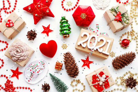 Christmas presents with decorations. New Year 2021 gifts in craft paper, pine cones, red hearts and confetti. Flay lay, top view background.