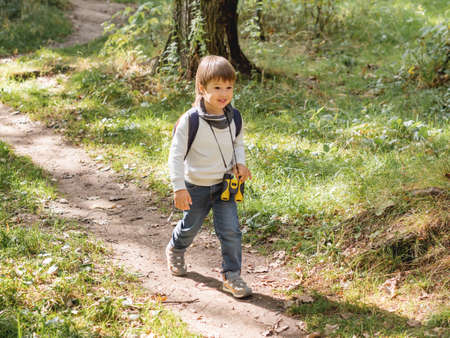 Curious boy is hiking in forest lit by sunlight. Outdoor leisure activity for kids. Child with binoculars and backpack.