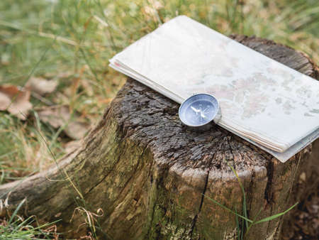 Compass and map lie on stump in forest. Tourist's gear for hiking. Summer adventure. Outdoor recreation. Active lifestyle. Archivio Fotografico