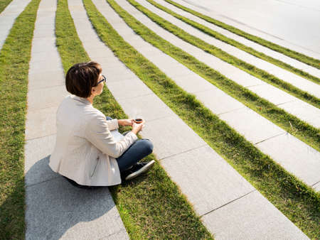 Young woman sits in park with take away cardboard cup of coffee. Casual clothes, urban lifestyle of millennials. Banque d'images