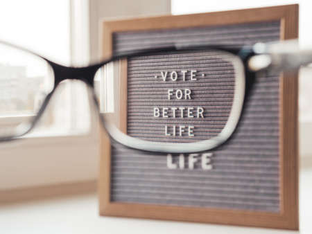 Letter board with words Vote for Better Life. Announcement of USA Presidential Election at 3rd November 2020. Call to go to the vote. Closer view on letter board through eyeglasses.
