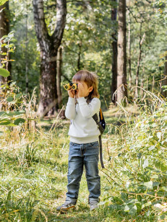 Curious boy is hiking in forest. Outdoor leisure activity for kids. Child looks through binoculars on tree foliage. Sunny day at autumn or summer day. Archivio Fotografico