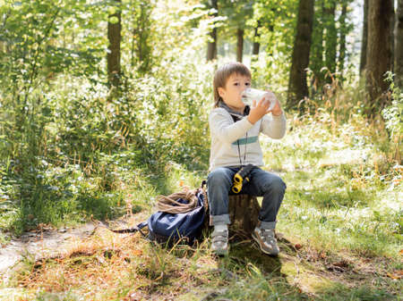 Little explorer on hike in forest. Boy with binoculars sits on stump and drinks water from bottle. Outdoor leisure activity for children. Summer journey for young tourist.