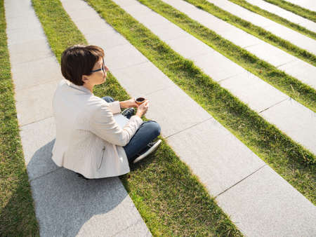 Woman with short haircut and eyeglasses sits in park with take away cup of coffee. Woman enjoys summer sun. Casual clothes, urban lifestyle of millennials. Banque d'images