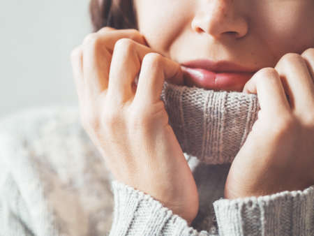 Close up portrait of woman snuggling in warm gray sweater. Casual outfit for cold weather at winter season. Banque d'images