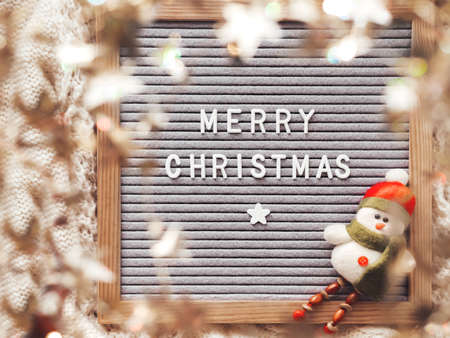 Letter board with season greeting Merry Christmas. Winter holiday spirit. Decorative snowman and shiny tinsel with stars.