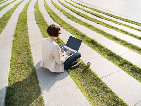 Freelance business woman sits in park with laptop and take away cardboard cup of coffee. Casual clothes, urban lifestyle of millennials. Working remotely. Stock Photo
