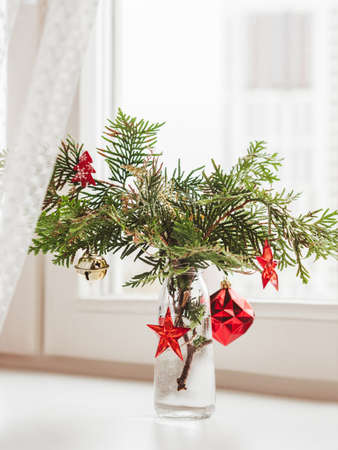 Vase with decorated thuja branches stands on window sill. Sustainable alternative for Christmas tree. Caring for nature. Refusal to cut down spruce forests. New Year celebration. Stock Photo
