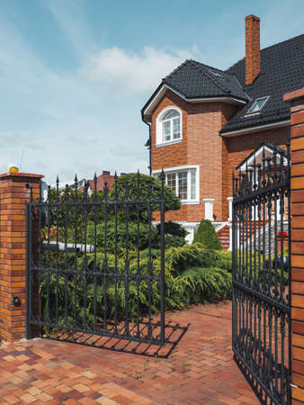 Gate is open to territory of house in suburbs of Kaliningrad. Well-kept brick building with manicured lawns. Russia. Stock Photo