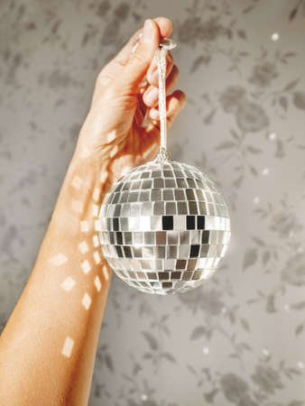 Woman holds sparkling on sun mirror disco ball. Light and shadow. Sunny morning at home. Sun reflections on walls. Symbol of music parties or holidays.