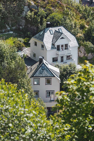 Two white houses in the middle of lush greenery in the suburb of Alesund. Norway. Stock Photo