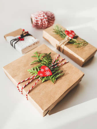 Christmas DIY presents wrapped in craft paper with fir tree branches and red hearts. Decorations on New Year gifts. Festive background. Winter holiday spirit.