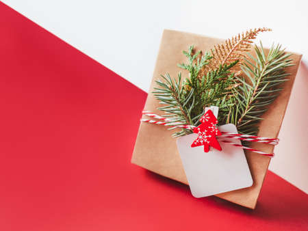 New Year present on geometrical white and red festive background. Gift wrapped in craft paper with fir tree twigs, red Christmas tree and clear tag. Copy space on label. Winter holiday spirit.