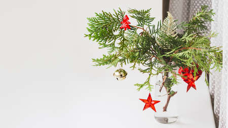 Vase with decorated thuja branches stands on window sill. Sustainable alternative for Christmas tree. Caring for nature. Refusal to cut down spruce forests. New Year celebration. Copy space.