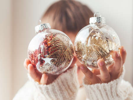Kid with decorative balls for Christmas tree.Boy in cable-knit oversized sweater.Cozy outfit for snuggle weather.Transparent balls with red, golden spangles inside.Winter holiday spirit.New year. Banque d'images