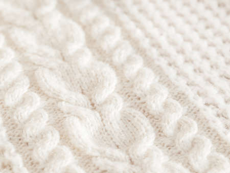 Hand made cable-knit sweater sweater. Texture of warm knitted fabric with pattern. White cardigan. Cozy autumn outfit for snuggle weather.