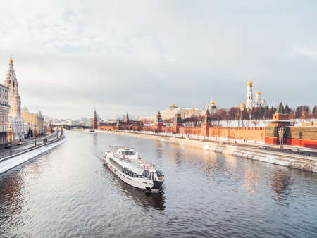View on touristic ship going down Moscow-river, Kremlin walls and bell tower of Ivan the Great. Winter sunset in historical center of Moscow, Russia. Фото со стока