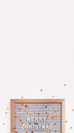 Letter board with Merry Christmas greeting and scattering golden confetti. New Year celebration. Copy space on white background. Vertical banner 9:16. 写真素材