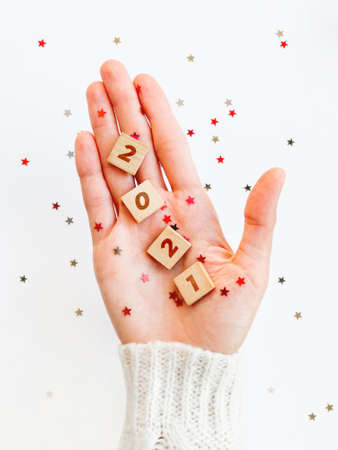 2021 on palm of hand. Woman in white knitted sweater holds wooden letters with stars confetti. Christmas and New Year background.