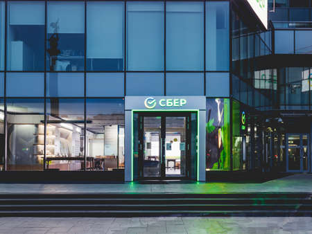 MOSCOW, RUSSIA - November 14, 2020. Facade of modern building. Entrance of Sberbank office with new glowing logo.