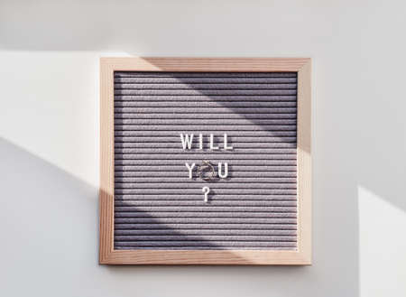 Top view on letter board with wedding proposal - Will You? Flat lay concept of creative way to impress future bride. Engagement ring with diamond.