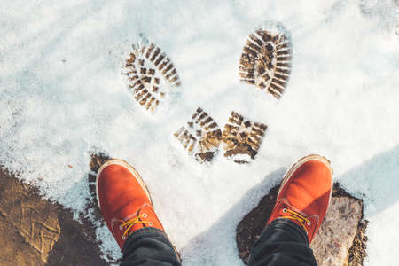 Woman in bright red shoes makes footprints in the snow. Sunny winter day. Top view on footmark with pattern. 写真素材