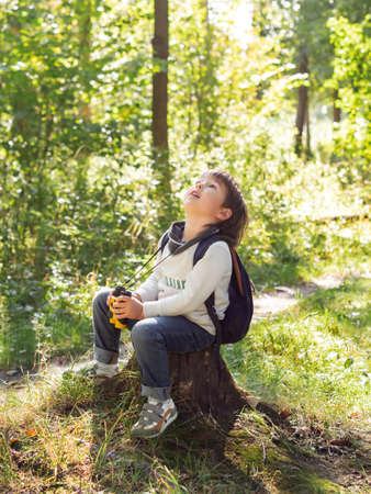 Little explorer on hike in forest. Boy with binoculars sits on stump. Outdoor leisure activity for children. Summer journey for young tourist. 写真素材