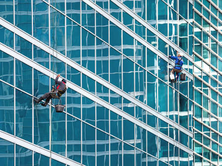Two industrial climbers with safety tethers wash the glass walls of modern skyscraper. Dangerous work in the metropolis.