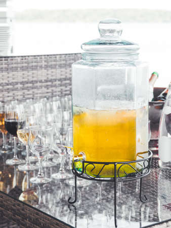 Glass decanter of cold lemonade. Transparent container with tap for soft drinks. Catering services for parties and celebrations. Outdoor bar.