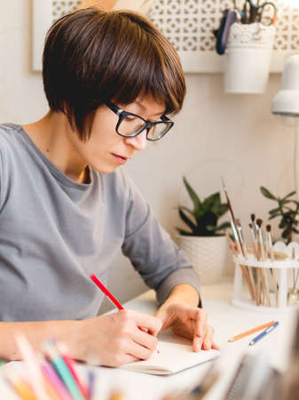 Woman with short hair cut is drawing in notebook. Calming hobby, anti stress leisure. Artist at work. Cozy workplace.
