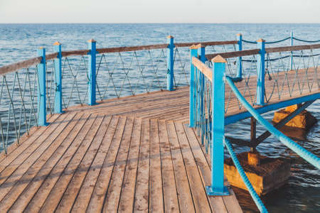 Wooden pier with blue railings. Coastal architecture. Pontoon over Red sea waves. Sunset light. Vacation.