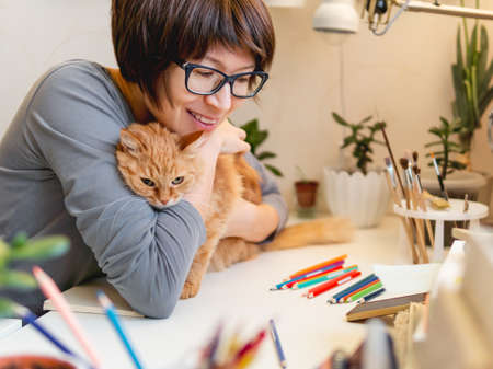 Woman with short hair cut hugs cute ginger cat. Fluffy pet and artist. Calming hobby, anti stress leisure. 版權商用圖片