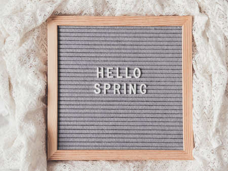Top view on gray letter board with season greeting HELLO SPRING. Crumpled white laces. Signs on textile background. 版權商用圖片