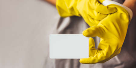 Man in gray robe puts on yellow rubber gloves and holds white card with copy space. Cleaning services for premises or announcement of sale in store of household supplies and crop production. 版權商用圖片