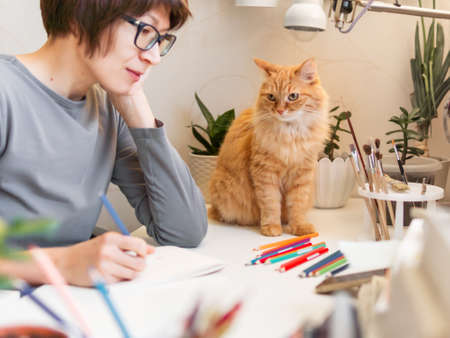 Woman with short hair cut is drawing in notebook. Cute ginger cat sits near her. Fluffy pet and artist. Calming hobby, anti stress leisure.