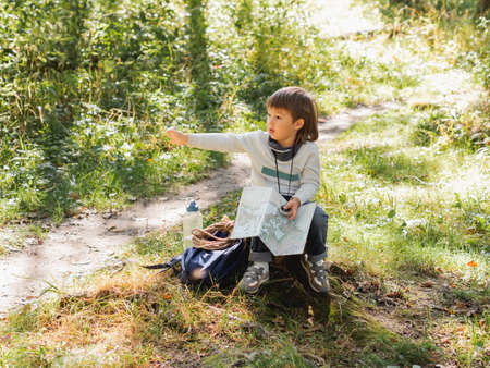 Little explorer on hike in forest. Boy with binoculars and compass sits on stump and reads map. Outdoor leisure activity for children. Summer journey for young tourist. Archivio Fotografico
