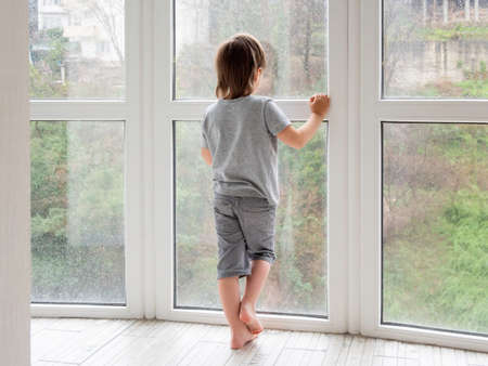 Little boy looks outdoors through wet panoramic window with raindrops. Rainy summer weather. Kid stays alone at home. Loneliness and sad mood without children's company. Coronavirus COVID19 quarantine.