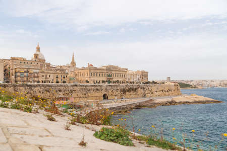 Panorama of Valletta, capital of Malta. Ancient buildings with old fashioned balconies and urban roads. Mediterranean sea embankment.