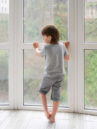 Little boy looks outdoors through wet panoramic window with raindrops. Coronavirus COVID19 quarantine. Rainy summer weather. Kid stays alone at home. Loneliness and sad mood without children's company.