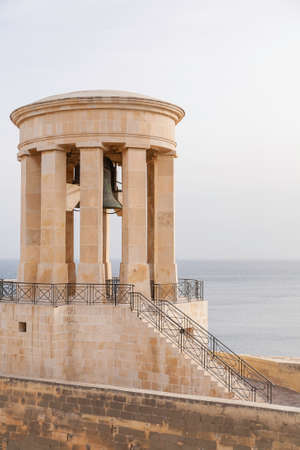 Siege Bell War Memorial Monument on cloudy sky and surface Mediterranean sea background. Architectural landmark in Valletta, Malta. Stock fotó