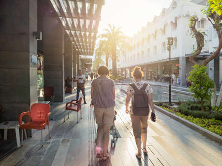 KEMER, TURKEY - May 13, 2018. Tourists walk down Munir Ozkul Liman street. Street with modern building, shops and flower beds.