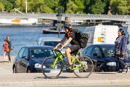 STOCKHOLM, SWEDEN - July 06, 2017. Woman in helmet and tracksuit rides bicycle along the sea embankment. Outdoor recreation. Cycling trip to Europe.