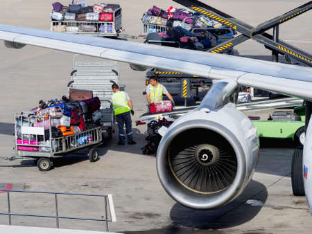 ANTALYA, TURKEY - May 22, 2018. Technical staff loads tourists' luggage on board of passenger plane at Antalya Airport. A lot of colorful suitcases fall into luggage compartment on conveyor belt. Redactioneel