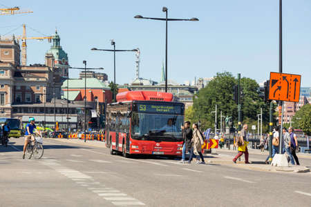 STOCKHOLM, SWEDEN - July 06, 2017. Traffic on urban road in capital of Sweden. Red public bus, cars and bicycles are waiting for green signal of traffic light. People cross road at pedestrian crossing.