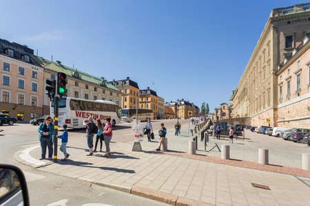 STOCKHOLM, SWEDEN - July 06, 2017. Tourists walk near The Royal Palace on Slottsbacken street. People on street lit with sunlight near architectural and historical landmark.